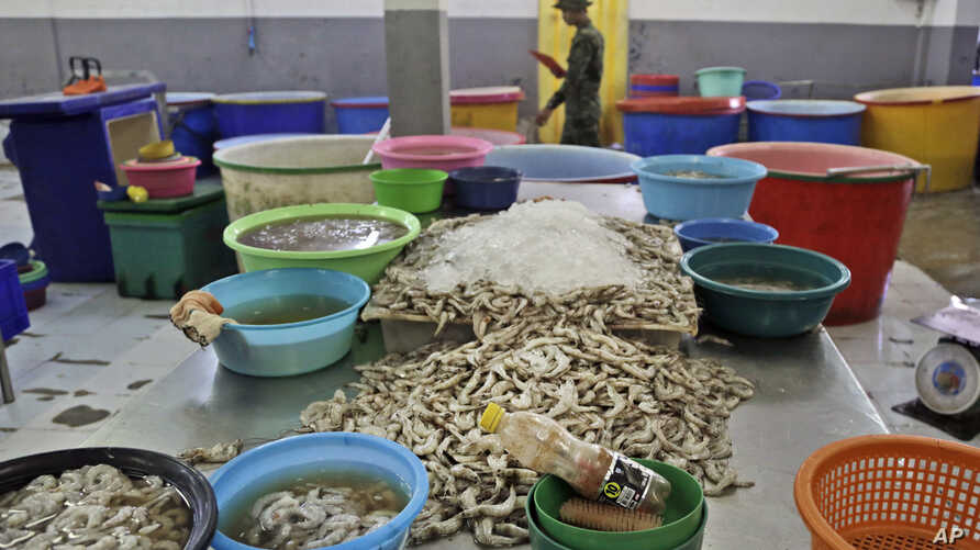 Shrimp are left on an abandoned peeling table as a Thai soldier walks past during a raid on the shrimp shed in Samut Sakhon, Thailand, Nov. 9, 2015. In November 2015, AP journalists followed and filmed trucks loaded with freshly peeled shrimp going f