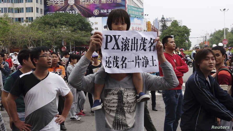 """A man carrying a girl on his shoulder holds up a paper reading """"PX (paraxylene petrochemicals) get out of Maoming, return us clean land"""", as demonstrators gather to protest against a chemical plant project, near the city government building in Maomin"""
