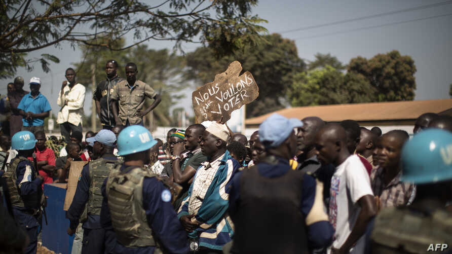 """Residents of the PK5 district hold a banner reading """"We want to vote"""" as they demonstrate in front of the MINUSCA, the United Nations mission in Central African Republic's headquarters, calling for more security measures outside of the polling statio"""