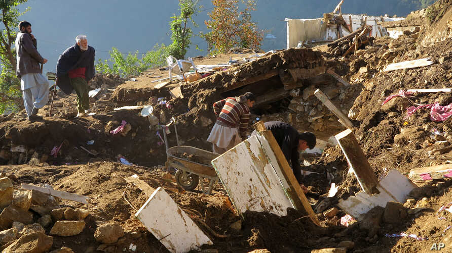 Pakistani villagers collect their belongings under the rubble of their homes destroyed from an earthquake in Shangla in Swat valley, Pakistan, Oct. 28, 2015.