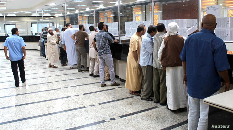 FILE - Libyan people gather in front of a counter in a bank to buy foreign currency in Misrata, Oct. 28, 2018.