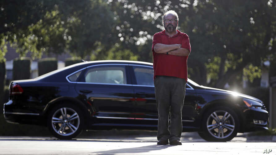 Bob Rand poses for a photo with his 2014 fully loaded Volkswagen diesel Passat, Sept. 23, 2015, in Pasadena, California.