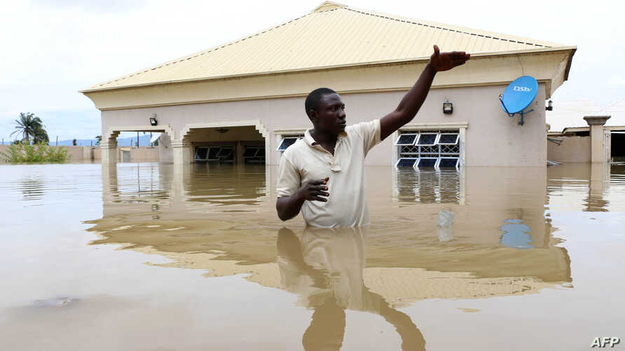 A man gestures next to his flooded house following heavy rain near the Nigerian town of Lokoja, in Kogi State, on Sept. 14, 2018.