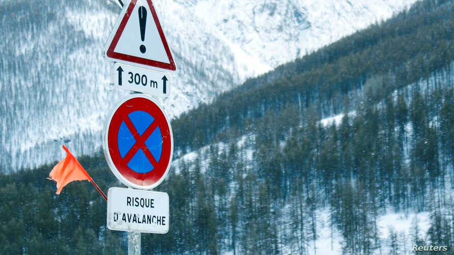 """Road signs are pictured on a snow-covered road in Saint-Pancrace as winter weather bringing snow and freezing temperatures continues in France, March 2, 2018. The sign reads, """"Avalanche risk."""""""
