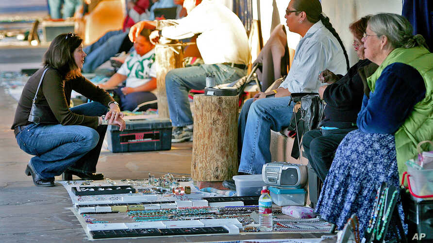 """In this file photo, sellers and buyers trade under the historic portal in Old Town Albuquerque, N.M. Feb. 8, 2006  Native American artists and crafts people say counterfeit """"tribal"""" art manufactured abroad devalues the market and cheats them out of b"""