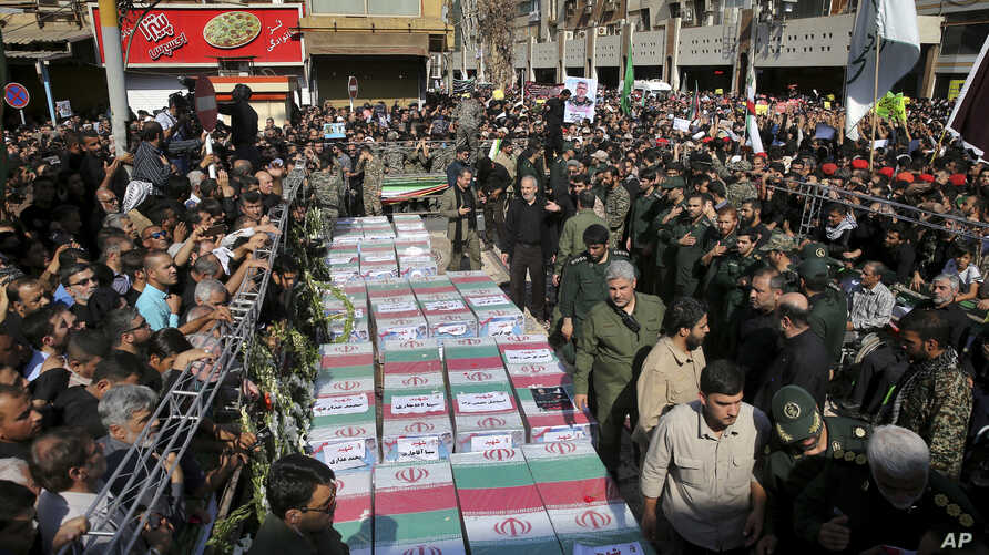 Flag-draped caskets of those who died in Saturday's terror attack on a military parade are laid out during a mass funeral, in the southwestern city of Ahvaz, Iran, Monday, Sept. 24, 2018.