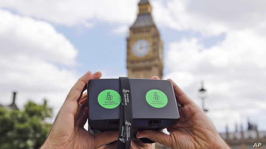 A man looks through a virtual reality device that shows a 360-degree view of the city of Aleppo, Syria, during an Amnesty International protest in Parliament Square, London, July 11, 2015.