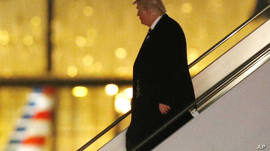 President-elect Donald Trump walks down the stairs from his plane after returning from Wisconsin to LaGuardia Airport, Dec. 13, 2016, in New York.