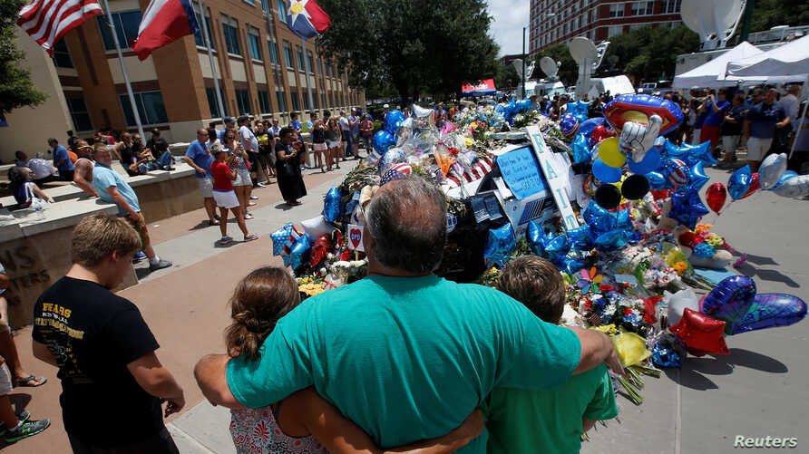 People hug at at a makeshift memorial at police headquarters following the multiple police shootings in Dallas, Texas, U.S., July 10, 2016.