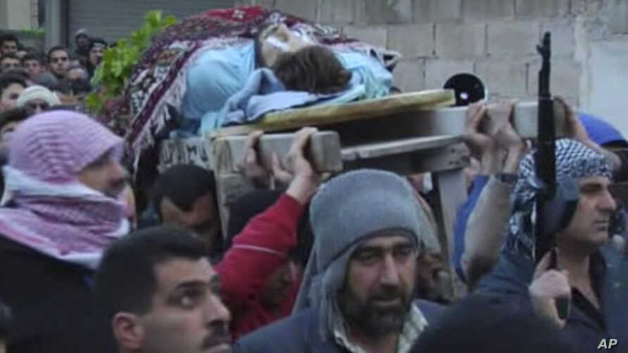 This image taken from video filmed over the past several days by an independent cameraman and made available February 7, 2012 shows a dead man carried outside in a funeral procession in Homs, Syria.