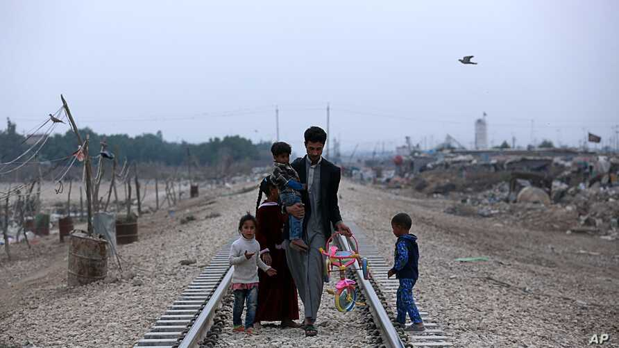 A homeless Iraqi family walks along railway tracks toward their hut, outside Baghdad, Iraq, Feb. 12, 2018.