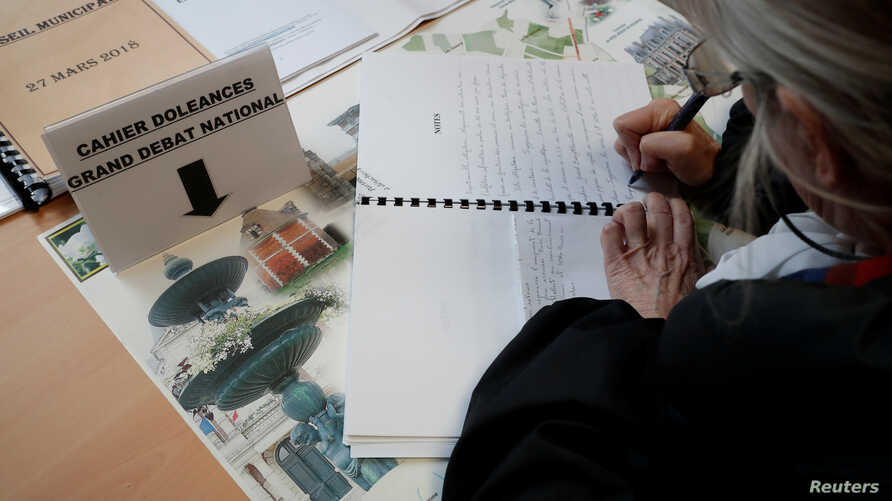 A woman writes in a book of grievances (Cahier de doleances) at the city hall on the eve of the launching of the 'Great National Debate' in Grand Bourgtheroulde, France, Jan. 14, 2019.