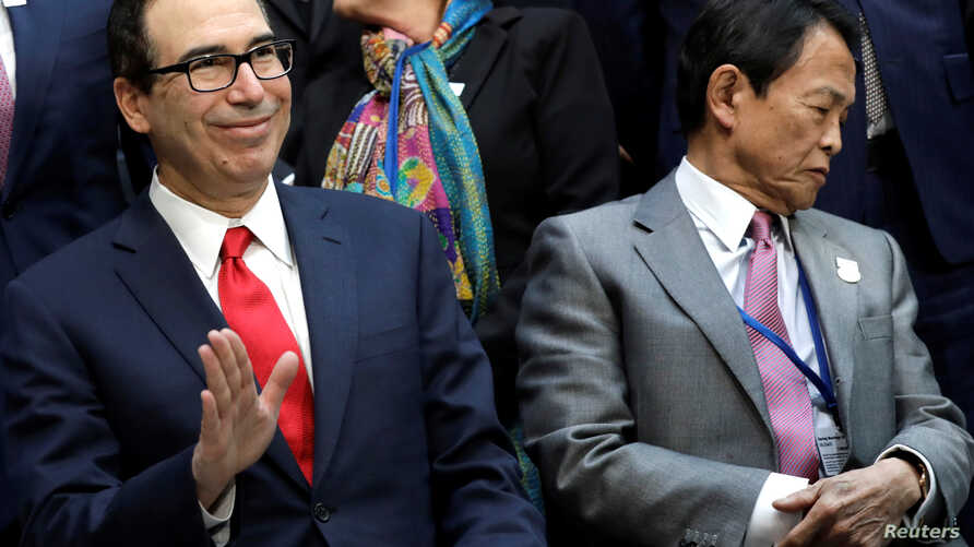 U.S. Treasury Secretary Steve Mnuchin waves next to Japan's Deputy Prime Minister and Finance Minister Taro Aso at the International Monetary Fund Governors family photo during the IMF/World Bank spring meeting in Washington, April 21, 2018.
