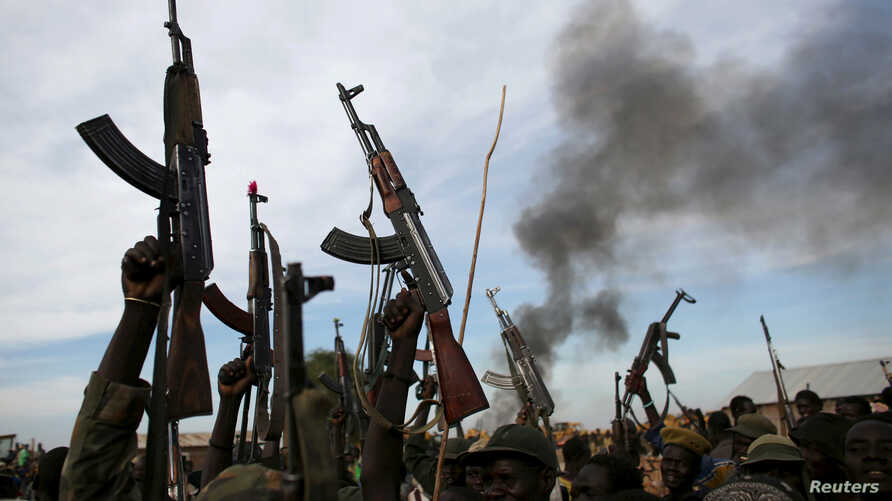 FILE - Rebel fighters hold up their rifles as they walk in front of a bushfire in a rebel-controlled territory in Upper Nile state, South Sudan Feb. 13, 2014.