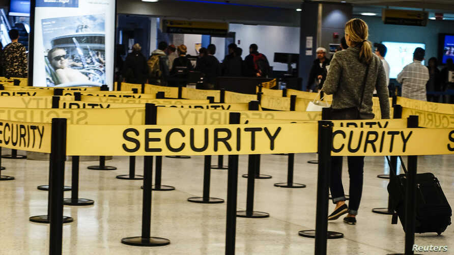 FILE - Passengers make their way in a security checkpoint at the International JFK airport in New York.