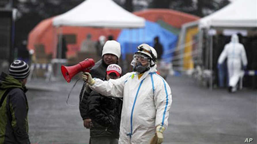 Officials wearing clothing to protect against radiation directs people to a center to scan residents who have been within 20 kilometers of the Fukushima Dai-ichi nuclear plant in Koriyama, Fukushima Prefecture, Japan, March 15, 2011