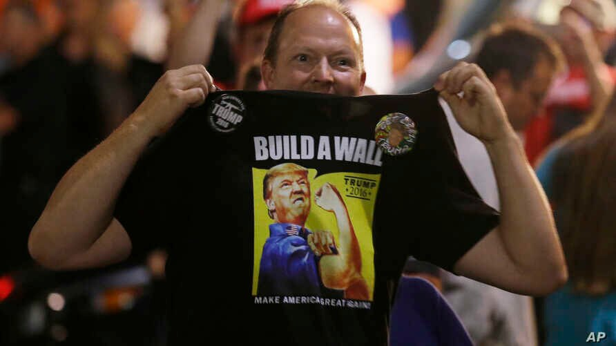 "A Donald Trump supporter holds up his shirt, which bears the slogan ""Build a Wall,"" at a campaign rally for Trump, Aug. 30, 2016, in Everett, Wash."