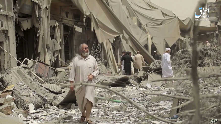 This undated frame grab from video posted online May 29, 2017, by the Aamaq News Agency, a media arm of the Islamic State group, shows people inspecting damage from airstrikes and artillery shelling in the northern Syrian city of Raqqa, the de facto ...