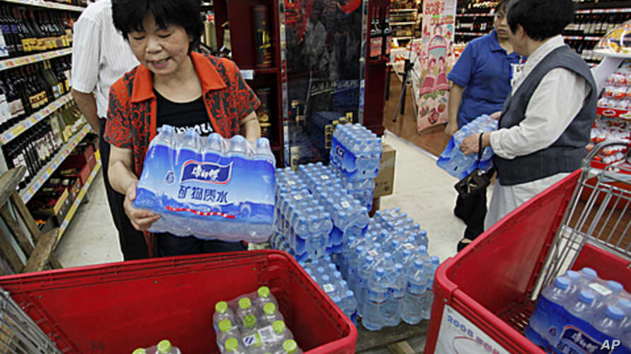 Customers stock cartons of bottled water at a supermarket in Hangzhou, Zhejiang province, after a local river, which is the source of drinking water, was polluted by a chemical leakage, June 6, 2011.