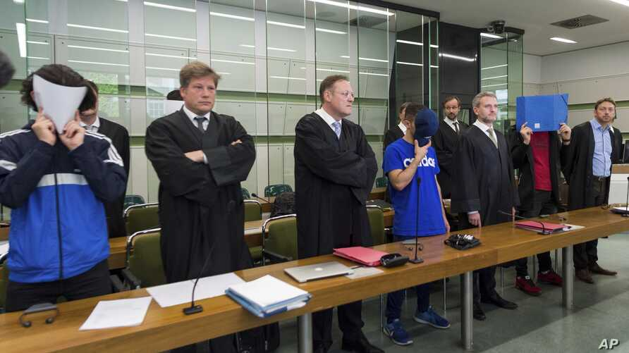 Three of the six young men accused of joint attempted murder in an attack on a homeless person hide their faces as they stand with their lawyers in the regional court in Berlin, Germany, June 13, 2017.