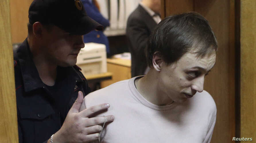 Bolshoi Theatre dancer Pavel Dmitrichenko is escorted out of a court room in Moscow, Nov. 6, 2013.
