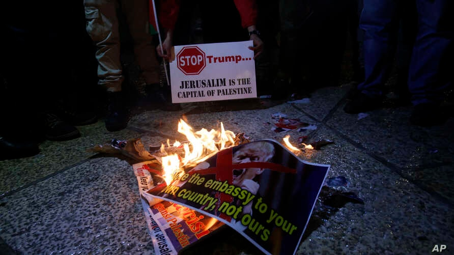 Palestinians burn a poster of the U.S. President Donald Trump during a protest in Bethlehem, West Bank, Dec. 6, 2017. Defying dire, worldwide warnings, President Donald Trump on Wednesday broke with decades of U.S. and international policy by recogni