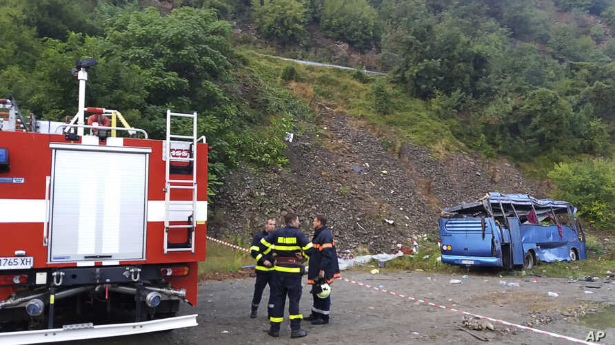 In this handout photo provided by the Bulgarian Interior Ministry, firefighters near the scene where a bus crashed and overturned, near the town of Svoge, Aug. 25, 2018.