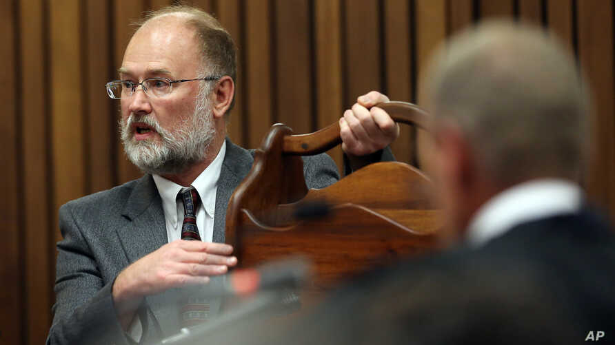 Forensic expert, Roger Dixon, left, holds a court exhibit, a magazine rack, as he answers questions put to him by chief state prosecutor Gerrie Nel , right, during the murder trial of Oscar Pistorius, in Pretoria, South Africa, April 17, 2014.