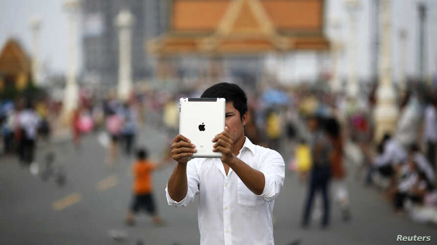 FILE - Lary, 27, takes a picture with his tablet in Phnom Penh.