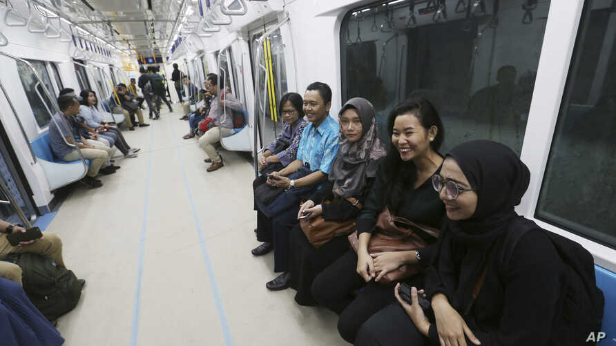 People ride on a Mass Rapid Transit (MRT) during a trial run in Jakarta, Indonesia, Feb. 21, 2019. The 10-mile system running south from Jakarta's downtown is the first phase of a development that if fully realized will plant a cross-shaped network o