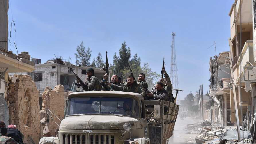 Syrian soldiers celebrate their victory against the Islamic State group in Qaryatain, Syria, April 4, 2016.