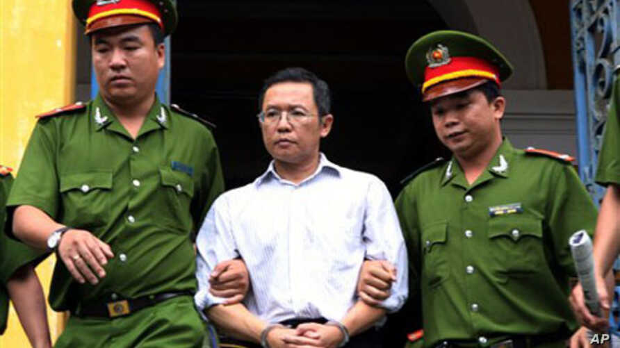 Police officers escort French-Vietnamese math professor Pham Minh Hoang out of a courthouse in Ho Chi Minh City, Vietnam. Aug. 10, 2011.