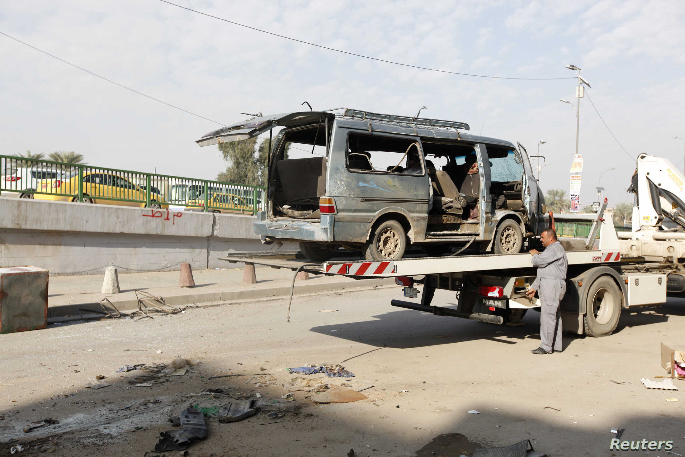 A worker prepares to remove the wreckage of a vehicle at one of the sites of car bomb attacks in Baghdad, Iraq, Dec. 8, 2013.