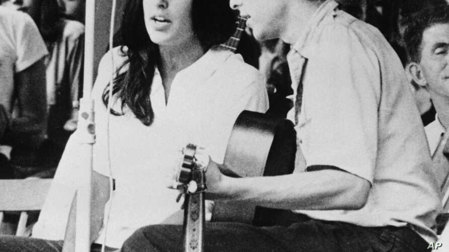 FILE - In this 1963 file photo, Joan Baez and Bob Dylan perform at the Newport Jazz Festival in Newport, R.I. Two years later,  at the same festival, Dylan plugged in an electric guitar and shocked the music world.