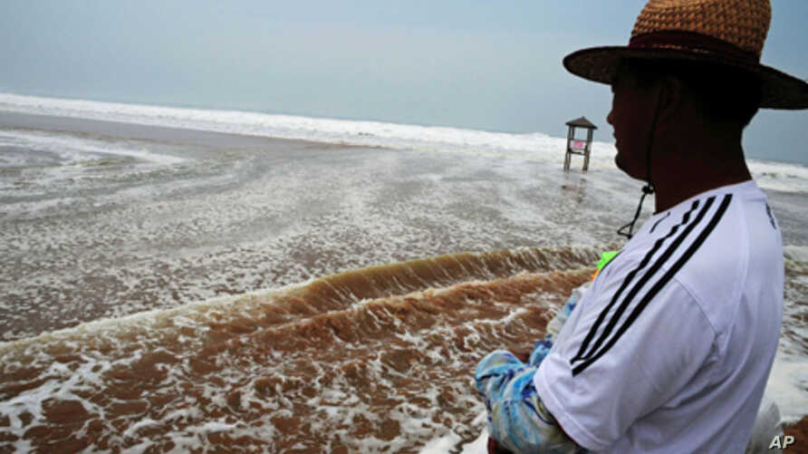 A Chinese man watches heavy seas by the coastline in Qingdao, in eastern China's Shandong province on Aug. 8, 2011, as typhoon Muifa traveled north, drenching the eastern province of Shandong.