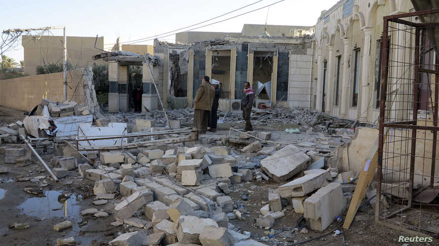 People gather at the site of a bombing in the city of Ramadi, west of Baghdad, Iraq, Nov. 6, 2014.