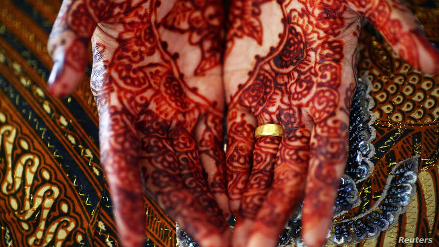 FILE - A bride shows her decorated hands and an engagement ring as she waits for her future husband to arrive for their wedding in Banda Aceh December 9, 2012.