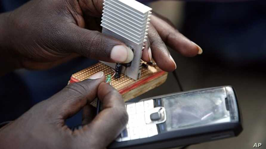 Jeremiah Murimi, a Kenyan electrical engineering student demonstrates how a 'smart charger' connected to a bicycle powers a mobile phone at the University of Nairobi. (File Photo)