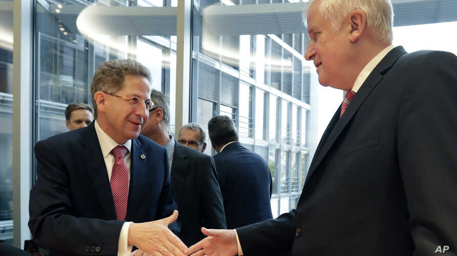 Hans-Georg Maassen, left, head of the German Federal Office for the Protection of the Constitution, and German Interior Minister Horst Seehofer, right, shake hands as they arrive for a hearing at the home affairs committee of the German federal parli