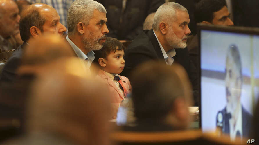 Yehiya Sinwar, left, a top Hamas official in Gaza, holds his son's Ibrahim, while sitting near Ismail Haniyeh, right, a former top Hamas official in Gaza, while listening to Khaled Mashaal, the outgoing Hamas leader in exile, during his news conferen