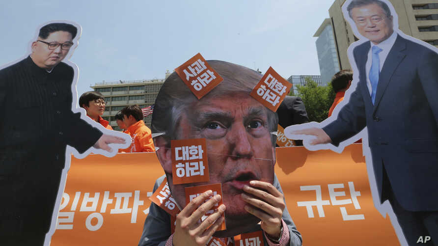 A protester wearing a mask of U.S. President Donald Trump, center, performs with cut-out photos of North Korean leader Kim Jong Un and South Korean President Moon Jae-in, right, during a rally against the United States' policies against North Korea ...