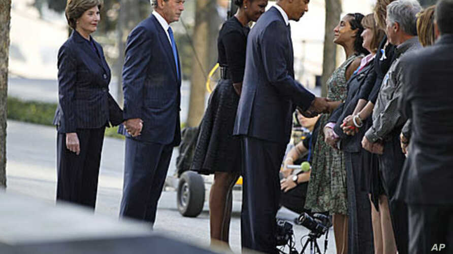 US President Barack Obama speaks with victims' relatives as he visits the north pool of the World Trade Center site with first lady Michelle Obama, former President George W. Bush and former first lady Laura Bush (L) during ceremonies marking the 10t