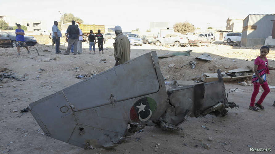 People stand next to the wreckage of a government MiG Libyan fighter jet that crashed during fighting Islamist fighters, in Benghazi, Libya, July 29, 2014.