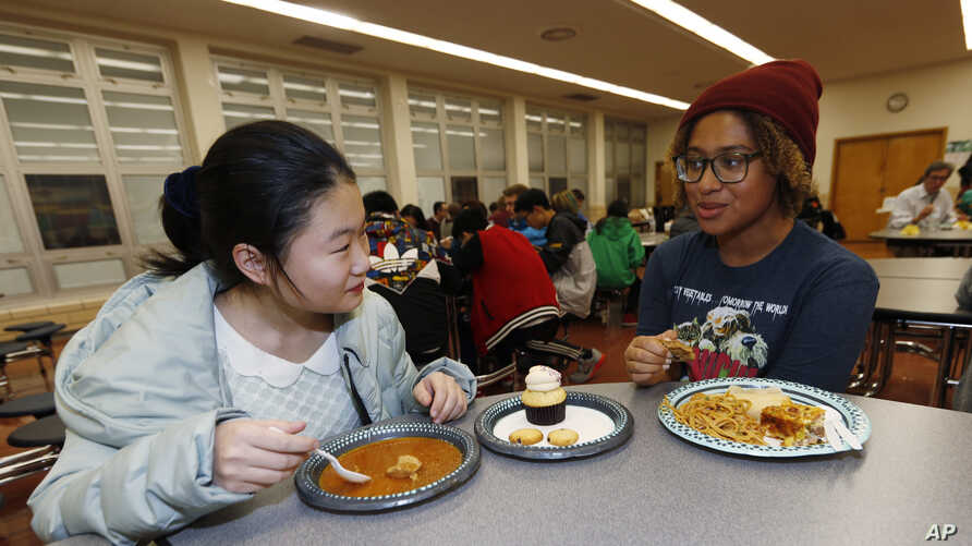 Foreign exchange student Miaofan Chen, left, of Hefei, China, chats with Thandi Glick during a potluck meal for Chinese exchange students and their families at a school in Denver, Jan. 27, 2017.
