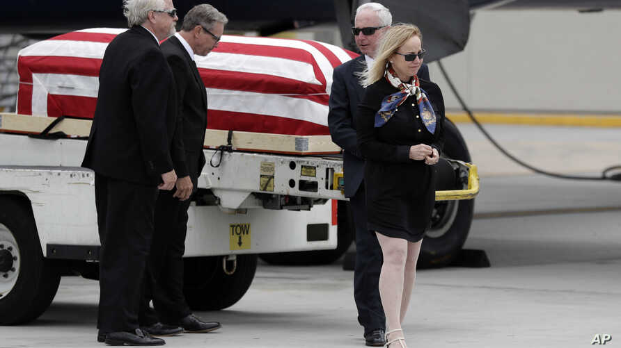 Deborah Crosby, right, walks away from her father's casket after its arrival to the airport, May 26, 2017, in San Diego.