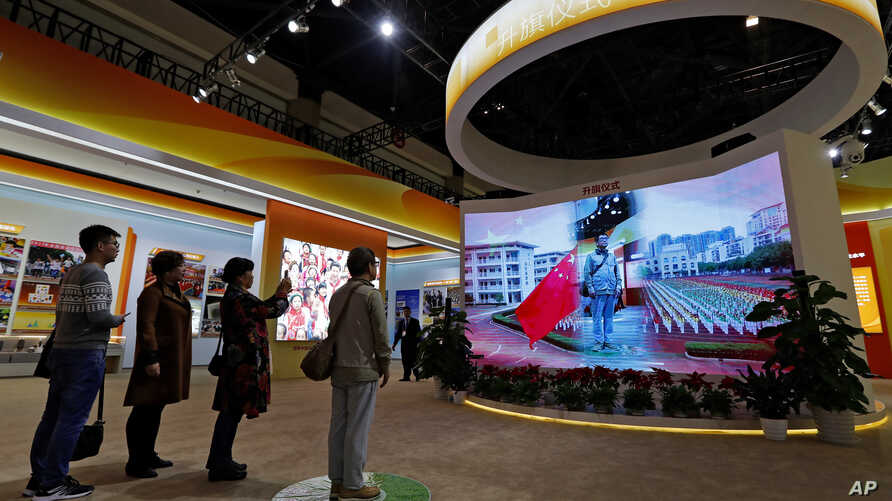 FILE - Visitors watch a man on a screen as he experiences a national anthem flag raising ceremony at an exhibition highlighting China's achievements at the Beijing Exhibition Hall in the capital city where the 19th Party Congress is held in Beijing,
