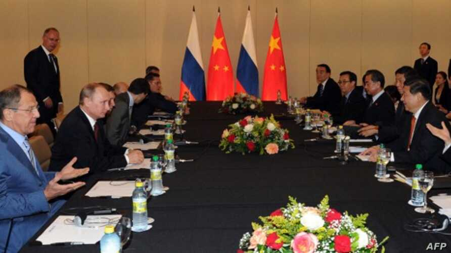 Russia's President Vladimir Putin (3rd L) holds talks with his China's counterpart Xi Jinping during their meeting on the sidelines of the BRICS group leaders summit  in Fortaleza, Brazil, on July 15, 2014, with Russia's Foreign Minister Sergei Lavro