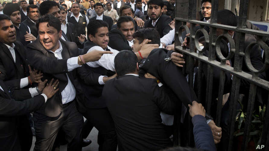 A lawyer, center, who spoke to the media supporting student leader Kanhaiya Kumar, is beaten up by other lawyers outside a Delhi court, in New Delhi, India, Feb. 17, 2016.