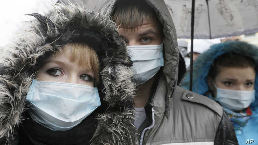 FILE - Ukrainians wearing medical masks demonstrate in front of the memorial monument to AIDS victims in Kiev, Ukraine.