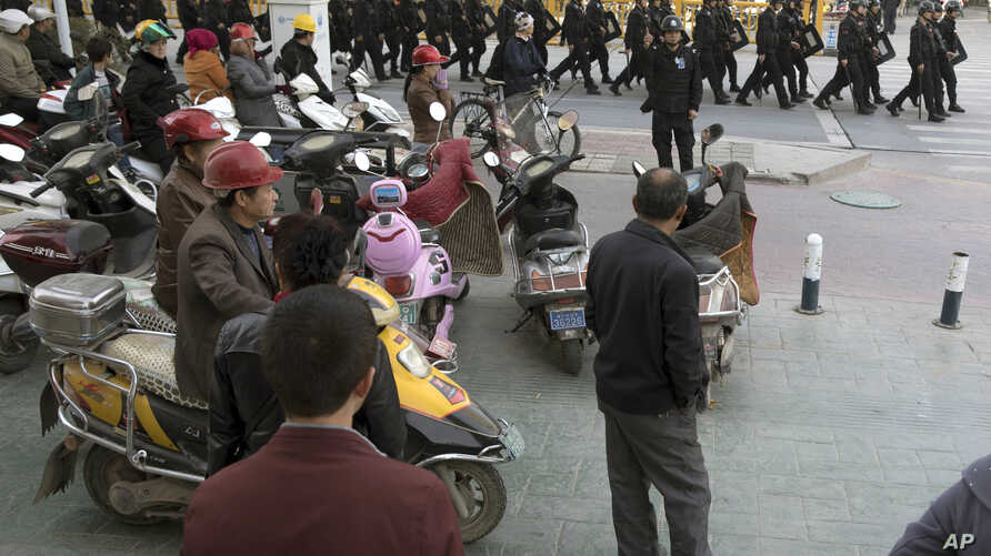 FILE - Residents watch a convoy of security personnel in a show of force through central Kashgar in western China's Xinjiang region, Nov. 5, 2017.